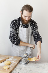 bearded man with apron making fresh pasta using pasta machine