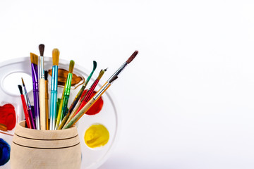 brushes in wooden bucket and paint palette, isolated