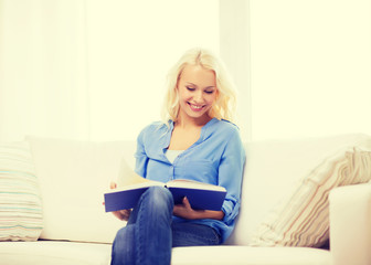 smiling woman reading book and sitting on couch