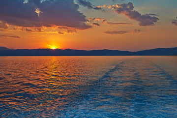 Sunset over the Greece, waves from the ferry, and the