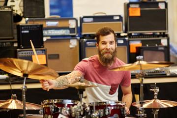 Spoed Foto op Canvas Muziekwinkel male musician playing cymbals at music store