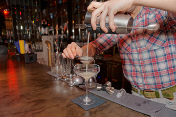 Bartender is straining drink in glass