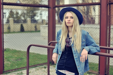 Portrait of a beautiful sad blonde girl outdoors in hat