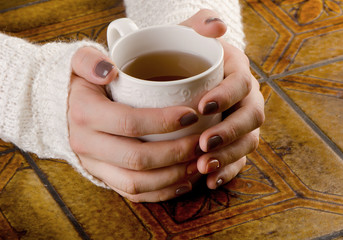 Woman holding white tea cup