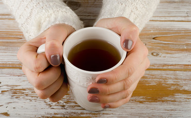 Woman holding tea cup over a wooden background