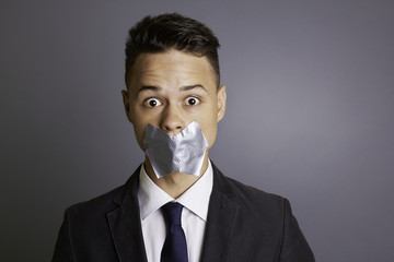 Businessman with tape over  mouth