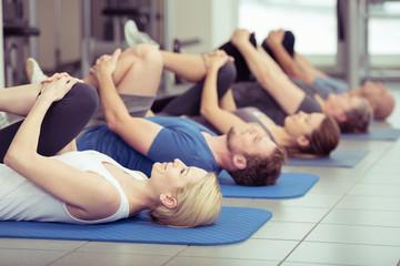gruppe macht dehnübungen im fitness-center