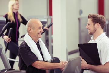 älterer mann schüttelt trainer die hand