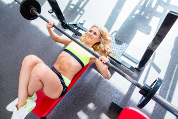 Woman at bench press in gym exercising for better fitness