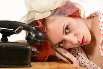 Redhead woman with a retro look waiting for the phone to ring