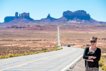 Female tourist poses  at the classic route to Monument Valley