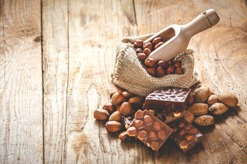 milk chocolate with hazelnuts and walnuts in a sack on a wooden