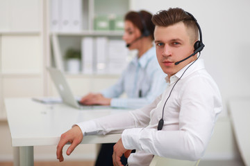 Businessman with headset smiling at camera in call center