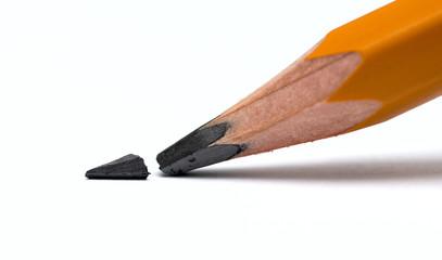 Broken head of sharp pencil on a white paper