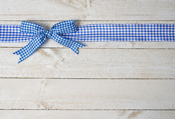 Blue ribbon on wooden background with copyspace