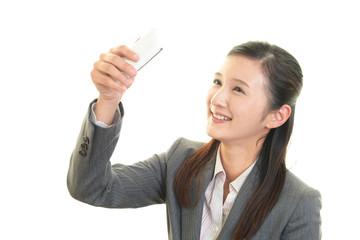 スマートフォンで自分の写真を撮る女性
