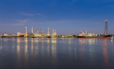 Panorama of Oil refinery at twilight along with river reflexion
