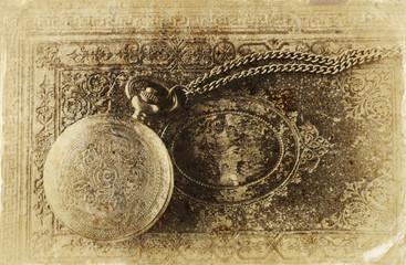 macro image of old vintage pocket watch on antique book. top vie
