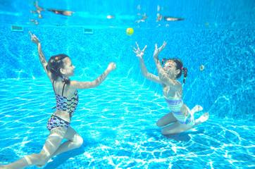 Kids swim in pool underwater, girls swimming and having fun