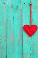 Red heart hanging on antique teal blue wood background