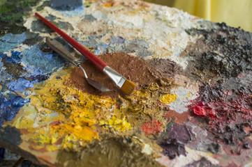 Focused trowel and brush on oil paint palette