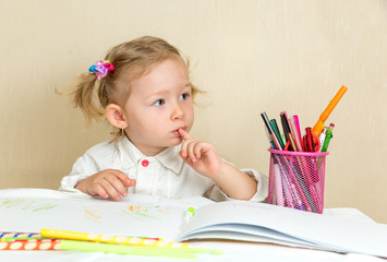 Cute child girl drawing with colorful pencils and felt-tip pen