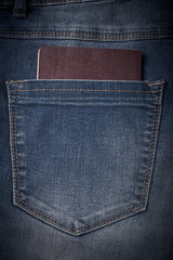 The pocket of jeans with document. Cloth background. Toned
