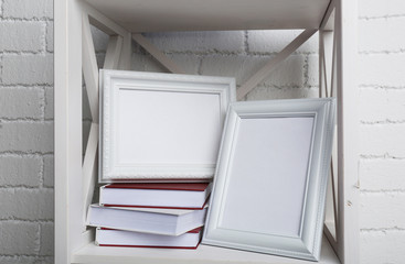 Photo frames with books on shelf, on brick wall background