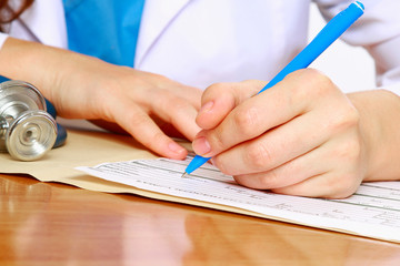 A female doctor is fiiling a prescription - close-up