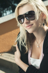 girl in sunglasses sitting on stairs