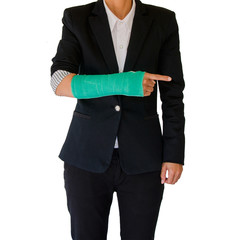 Injured businesswoman with green cast on hand and arm on white b