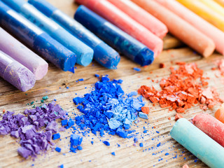 Rainbow colored pastel crayons with crushed chalk close up on ol