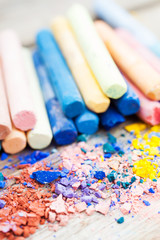 Pile of crushed chalk closeup and rainbow colored pastel crayons