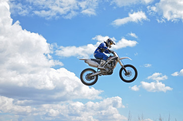 Motocross driver standing on the MX bike is flying over the