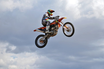 Canvas Print - Rider by motorcycle MX flies over the hill against the blue sky