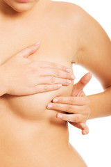 Topless woman examining her breast