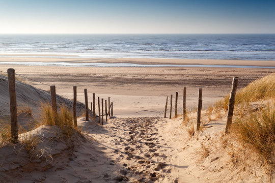 sand path to North sea at sunset