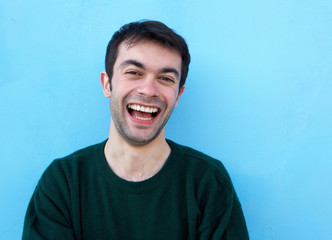 Close up portrait of a cheerful young man laughing