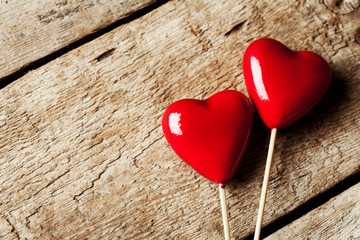 Valentine day concept:  two red hearts on wooden background