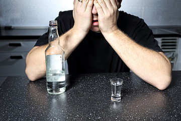 Addicted to alcohol man with bottle of vodka