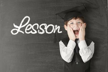 Cheerful little boy on blackboard. Looking at camera