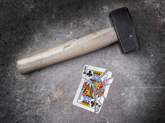 Hammer with a broken card, king of clubs