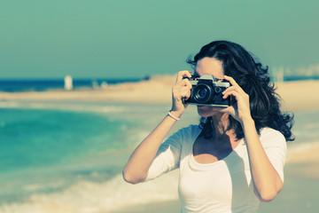 Woman with vintage retro camera having fun on the beach on blue
