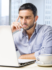 attractive businessman on computer at business district office