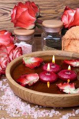 Spa concept with roses, pink salt and candles that float in wate