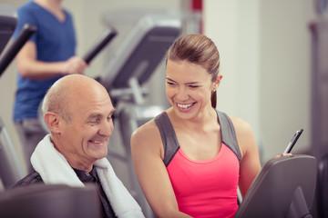 lächelnde trainerin im fitness-club berät senior