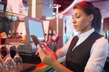 Pretty barmaid using touchscreen till