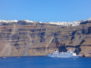 Fototapete - Little cruise ship in Santorini, Greece