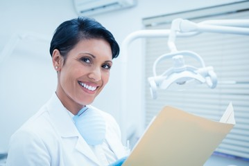 Smiling female dentist reading reports