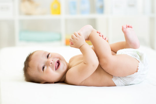 baby lying on white bed and holding legs